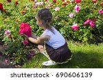 Stock photo happy little girl in a garden with red roses 690606139