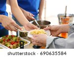 Volunteers Giving Food To Poor...
