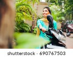 indian woman riding motorbike | Shutterstock . vector #690767503