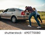 man and woman pushing a broken... | Shutterstock . vector #690770080