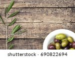 Small photo of Background with purple and green olives and olive branch on a wooden background. Rustic Italian still life, top view