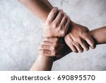 Small photo of Close up top view of young people putting their hands together showing unity and teamwork.