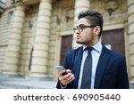 young man in suit standing in... | Shutterstock . vector #690905440