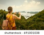 hiker with backpack enjoying on ... | Shutterstock . vector #691001038