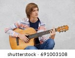 Small photo of Talented teenage boy with trendy hairdo wearing shirt and jeans holding acoustic guitar playing his favourite songs while sitting against grey concrete wall, People, talent, lifestyle, music concept