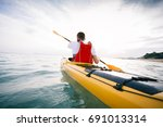 rear view of kayaker paddling. ... | Shutterstock . vector #691013314