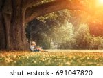 little boy reading a book under ... | Shutterstock . vector #691047820