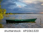 boat on the shore of lake... | Shutterstock . vector #691061320