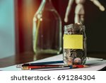 saving money into the bottle on ... | Shutterstock . vector #691284304