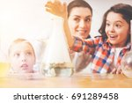 Small photo of Positive delighted pupil holding her hand above smoking flask