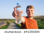 young sporty man show bottle of ... | Shutterstock . vector #691350304