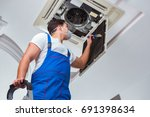 worker repairing ceiling air... | Shutterstock . vector #691398634