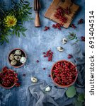 Small photo of red currant and quail eggs in bowls with wooden desk, wooden juicer, yellow flower and green leaves on a blue background, top view