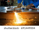 man cutting metal with fire... | Shutterstock . vector #691449004