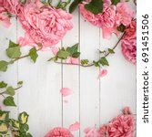 Stock photo vintage styled image of pink roses lying on white wooden background with copy space inspired by 691451506
