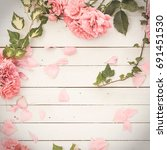Small photo of vintage styled image of pink roses lying on white wooden background, with copy space, inspired by flat lay style with matte effect