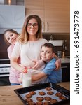 mom and her son bake cookies at ... | Shutterstock . vector #691473778
