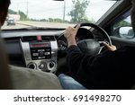 Right hand drive car. Man hands holding steering wheel.