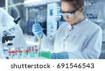 female research scientist uses... | Shutterstock . vector #691546543