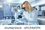 female research scientist looks ... | Shutterstock . vector #691546594