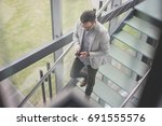business man walking on the... | Shutterstock . vector #691555576