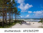 Baltic sea shore in Latvia. Sand dunes with pine trees and clouds. Typical Baltic beach landscape