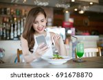 young asia woman eating food at ... | Shutterstock . vector #691678870