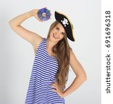 Small photo of Nice young woman with pirate cd or dvd disk and hat with skull and crossbones. Concept of software piracy and copyrighting