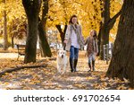 Stock photo family woman and her daughter walk autumn park with his dog golden retriever 691702654