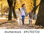 Stock photo family woman and her daughter walk autumn park with his dog golden retriever 691702723