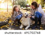 Stock photo family woman and her daughter walk autumn park with his dog golden retriever 691702768