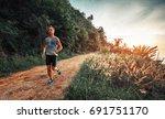 athletic man runs on a rural... | Shutterstock . vector #691751170
