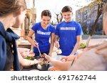 volunteers sharing food with... | Shutterstock . vector #691762744
