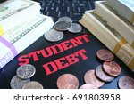 Small photo of Student Debt Written On Laptop Keyboard With Stacks Of Money
