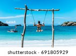 Small photo of Young traveler guy is standing on swing on the beautiful beach in Bali. He is enjoying the Gloomy sand beach with the turquoise sea background at the paradise of indonesia. backpacker make a trip .