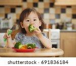 baby girl eating broccoli | Shutterstock . vector #691836184