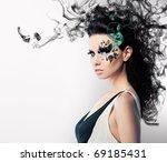 face art of rhinestones on brunette woman and smoke - stock photo