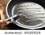 woman pouring oil into frying... | Shutterstock . vector #691855018