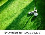 golf ball with putter on green... | Shutterstock . vector #691864378