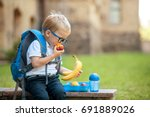 Cute schoolboy eating outdoors...