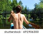 man paddles down river  | Shutterstock . vector #691906300