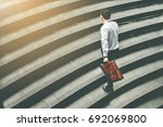 Small photo of Young Asian businessman holding Brown leather bag working on staircase go office hurry work time with sunset top view and vintage tone