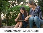 happy asian daughter drawing... | Shutterstock . vector #692078638
