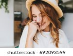 Stock photo close up photo of amazing happy girl with pale skin shy laughing and cover face with hand indoor 692093599