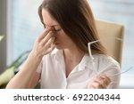 Tired Woman Massaging Nose...