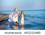 mother and daughter on the beach | Shutterstock . vector #692221480