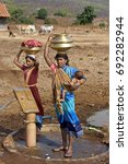 Small photo of May 17th 2010 Dindori District Madhya Pradesh India Baiga tribal woman fetching potable Borewell drinking water in a village in brass vessels