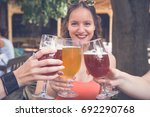 Small photo of Female toasting and cheering aperitif beers half pint with her friends at restaurant