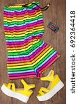 Small photo of Colorful striped sleeveless romper, yellow wedge sandals and wide multicolored bracelet. Summer fashion. Trendy outfit for women