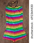 Small photo of Multicolored striped sleeveless romper on dark wooden surface. Trendy summer piece of clothing for women